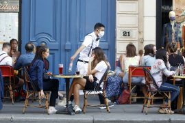 A waiter wearing a face mask serves clients while people eat and have drinks on the terrace of the cafe-restaurant  in Paris on June 2, 2020, as cafes and restaurants reopen in France with the easing of lockdown mesures taken to curb the spread of the COVID-19 pandemic, caused by the novel coronavirus. French cafes and restaurants reopened their doors on June 2 as the country took its latest step out of coronavirus lockdown, with clients seizing the chance to bask on sunny terraces after 10 weeks of closures to fight the outbreak.     (Photo by Mehdi Taamallah/NurPhoto via Getty Images)
